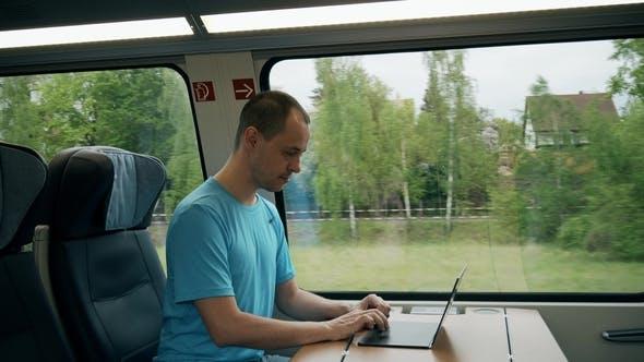Thumbnail for Mann arbeitet auf seinem Laptop während der Reise mit dem Zug