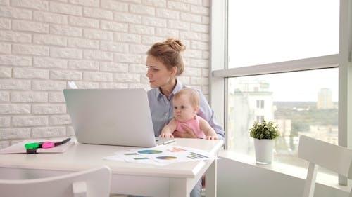Geschäftsfrau mit Kind Arbeiten mit Dokumenten. Freelancer im Mutterschaftsurlaub
