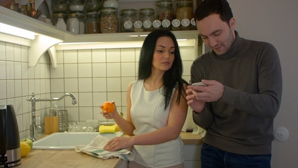 Thumbnail for Happy Couple Talking and Using Smartphone While Cooking in Kitchen at Home