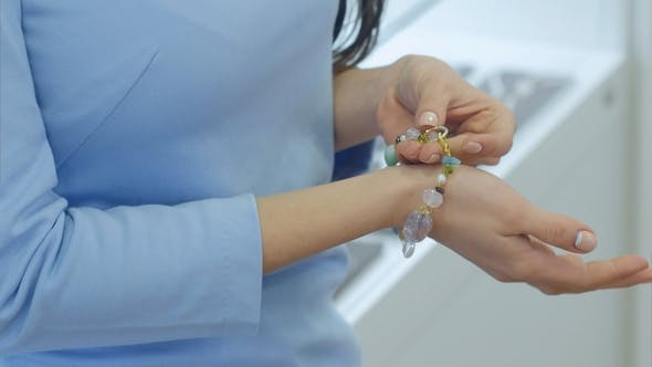 Thumbnail for Beautiful Young Woman Trying on Necklace with Designed Bracelet on Her Hand