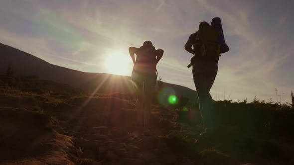Thumbnail for Climbing the Mountain at Dawn. Two Tourists Climb Up the Mountain Path in the Sun
