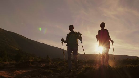 Cover Image for Romance of an Active Way of Life. A Couple of Tourists in the Rays of the Setting Sun Go Along the