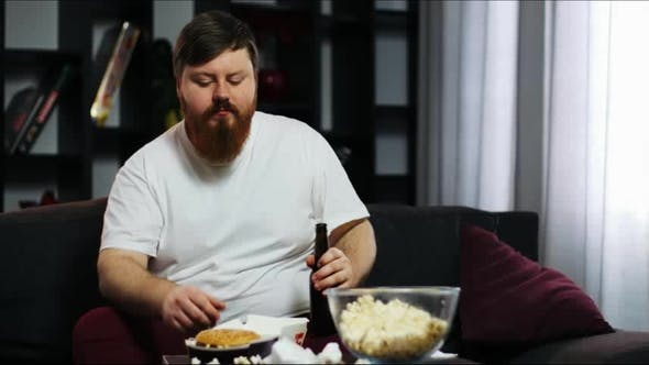 Thumbnail for Funny Fat Guy Eating Fast Food, Drink Beer and Doing Dumbbell Training. He Is Sitting at Home on the