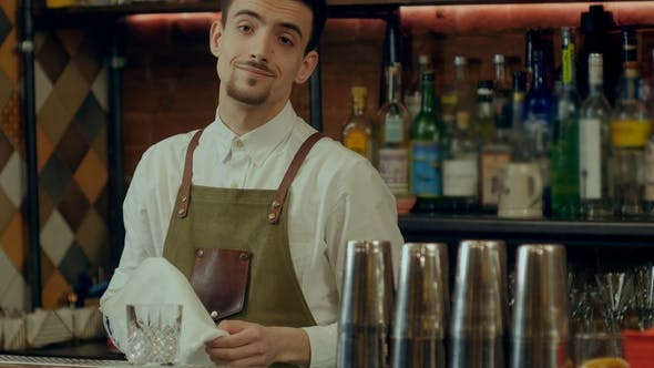 Thumbnail for Barman at Work Rubs a Glass Looking to a Camera