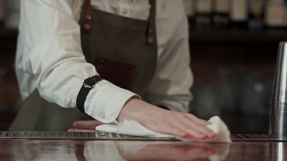 Thumbnail for Barman at Work Rubs Wooden Table with Napkin