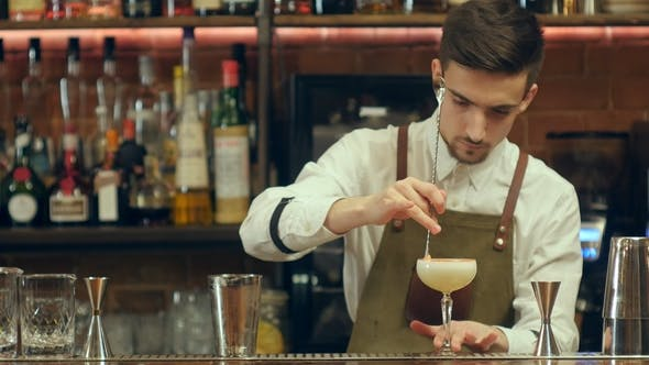 Thumbnail for Bartender Making and Decorating Cocktail To a Visitor