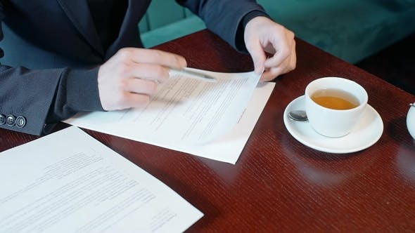Thumbnail for Hands of Businessman Reading Contract in the Cafe.