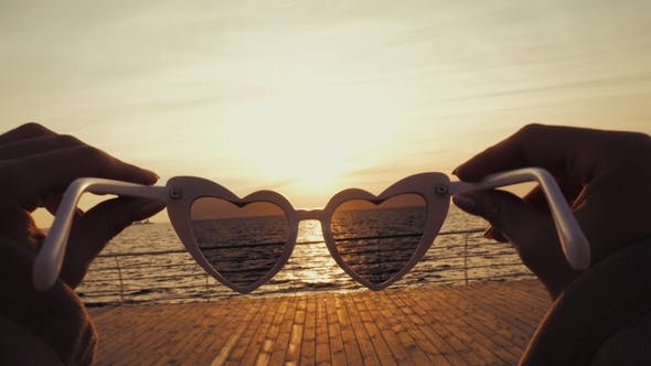 Thumbnail for Girl Puts on Vintage Heart-shaped Sunglasses on the Camera and Looks at the Sea. First-person View