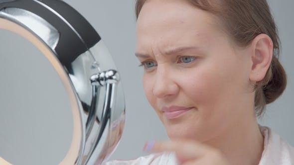 Thumbnail for Caucasian Woman with Mirror with Ring Light with No Makeup Look Examine Her Skin and Makes Facial