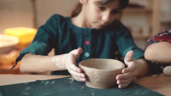 Thumbnail for Child Is Making a Plate of Clay. a Lesson in Pottery. Little Girl Makes Patterns on a Clay Stamp