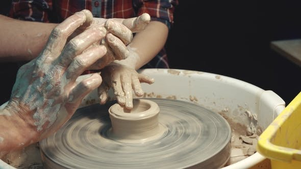 Thumbnail for Teacher Teaching the Child to Form Clay on a Potter's Wheel
