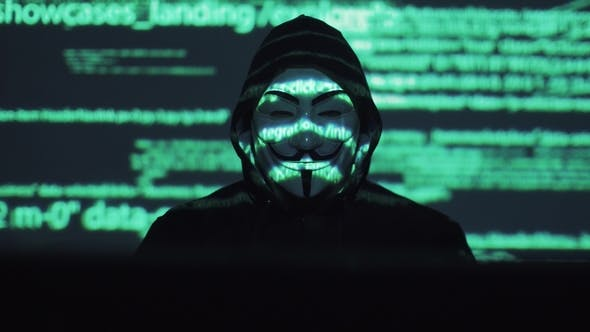 Theft of Personal Data on the Network. Robber in the Mask and Hood Against the Background of the