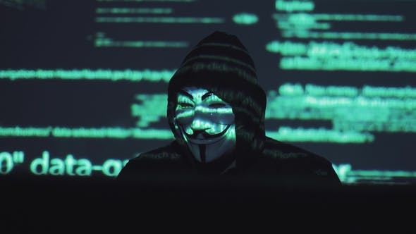Thumbnail for A Male Robber in a Mask Works on a Computer in a Dark Room. Computer Code Is Reflected on His Face