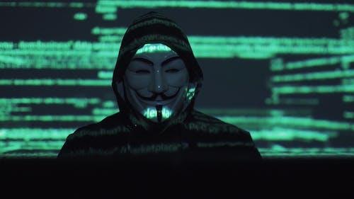 Hacker in der Maske hackt das Programm