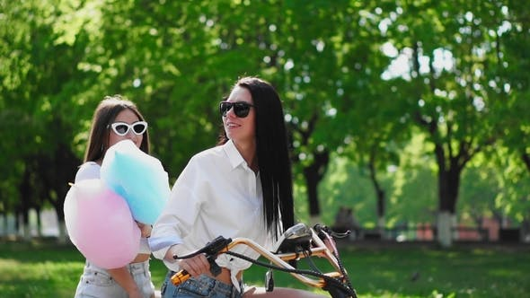 Thumbnail for Two Beautiful Girls in Denim Shorts Ride in the Park on an Electric Scooter in the Summer