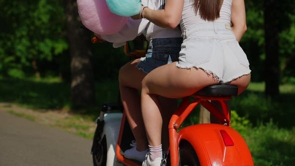 Thumbnail for Two Beautiful Girls in Denim Shorts Ride in the Park on an Electric Scooter in the Summer in  Rea