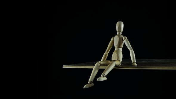 Wooden Figure Dummy Procrastinates in Studio on Black Background Sitting and Waving Legs
