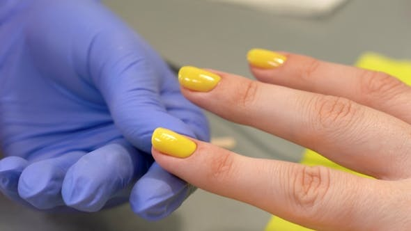Thumbnail for of Fingernail Shape Correction Using Nail File. Yellow Polish. Last Manicure Strokes. Beauty Salon.