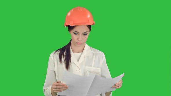 Thumbnail for Young Engineer Woman Wearing Safety Helmet Examining Technical Drawings on a Green Screen, Chroma