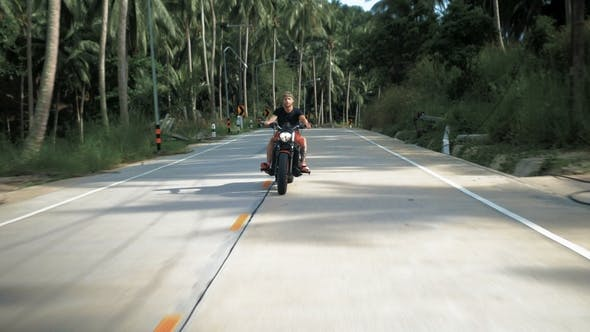 Young Man Without Helmet Riding His Orange Motorcycle, Stabilized Shot