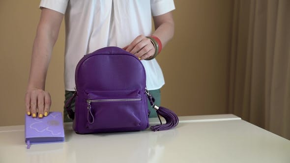 Thumbnail for A Young Woman Takes Out the Contents of Her Purple Backpack and Puts All Things on a White Table