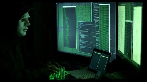 Anonymous Man Hacking Computers in Dark Room