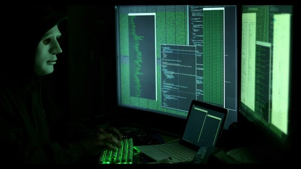 Thumbnail for Anonymous Man Hacking Computers in Dark Room