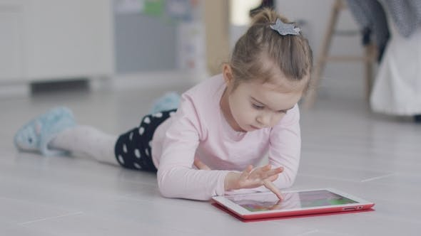 Thumbnail for Relaxing Girl Playing Tablet on Floor