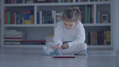 Interested Girl with Tablet on Floor