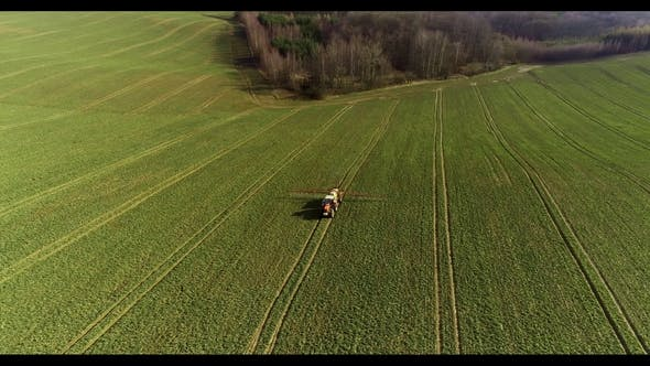 Tractor Spray Fertilize on Field with Chemicals in Agriculture Field