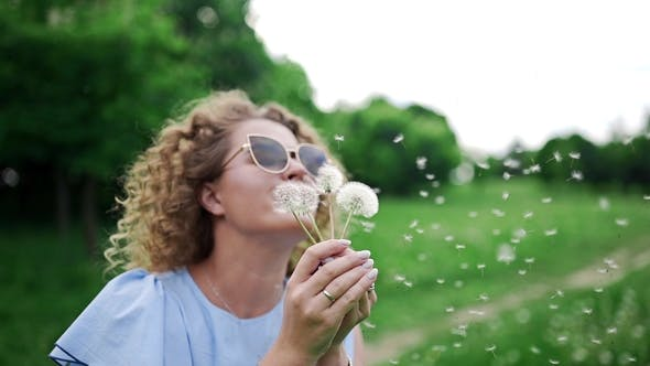 Thumbnail for Attractive Woman in Sun Glasses Blows the Dandelions and They Fly Away on the Wind