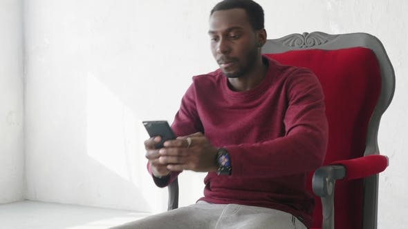 Thumbnail for Black Man Uses a Smartphone To Communicate on the Internet
