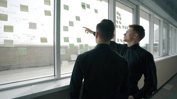Thumbnail for Young Men Are Talking, Pointing on Notes on Window in Modern Office