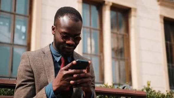 Thumbnail for Young African American Man Sitting on a Bench and Typing on His Smart Phone. Business and Lifestyle