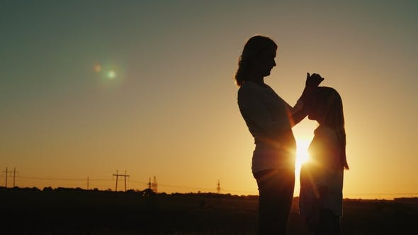 Cover Image for Mother Caresses Her Daughter Gently on the Head at Sunset. Mom with a Baby Concept