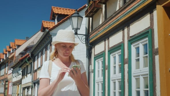 Cover Image for A Tourist with a Phone in Her Hands Is Walking Along the Beautiful Street of a European City.