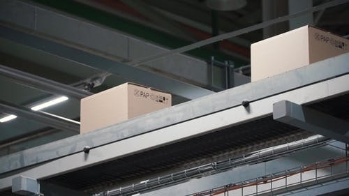 Automation - Cardboard Boxes on Conveyor Belt in Factory. Clip. Boxes Moving on the Conveyor at the