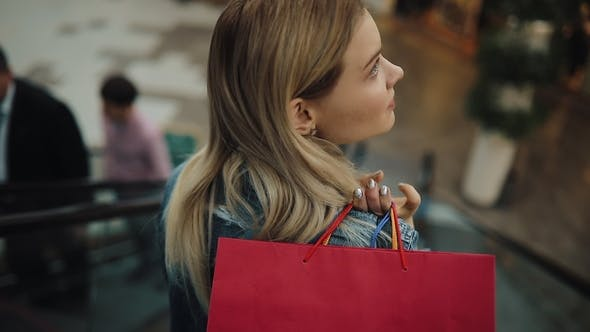 Thumbnail for Young Blonde Woman in Jeans Jacket Smiles Going Down on the Moving Staircases in the Shopping Mall