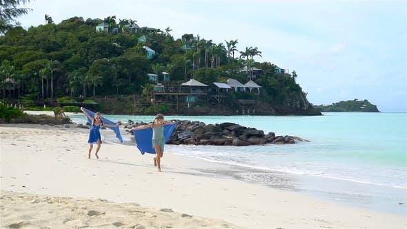 Thumbnail for Little happy funny Mädchen haben eine Menge Spaß bei tropischen Strand spielen zusammen