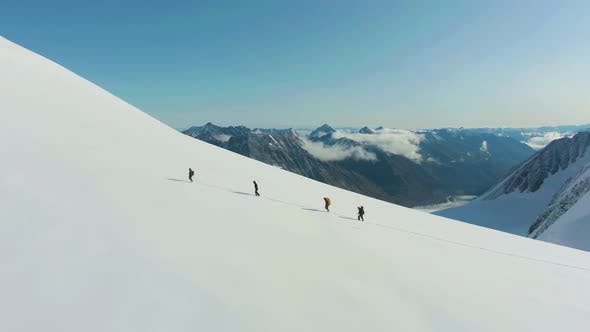 Group of Alpinists Is Advancing As Roped Team in Snowy Mountains. Aerial View