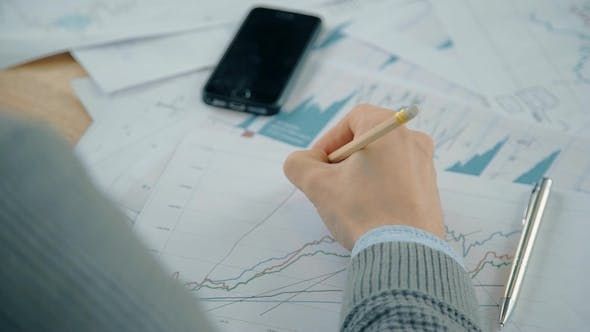 Thumbnail for Hand of Businessman Working on Graph with Market Situation at the Table in the Office