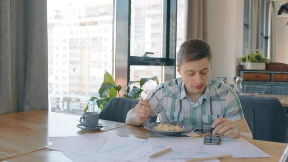 Thumbnail for Young Businessman Is at Business Lunch, Using Phone Sitting in Cafe