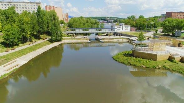 Thumbnail for Fluss fließt durch die Stadt und umgeben von grünen Pflanzen