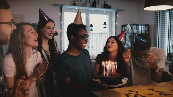 Thumbnail for Happy African American Man hält Geburtstagskuchen, Tanzen und Feiern bei multiethnischen Party mit