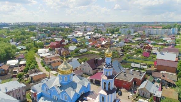 Thumbnail for Orthodoxe Kirche mit funkelnden Kuppeln gegen Stadtgebäude