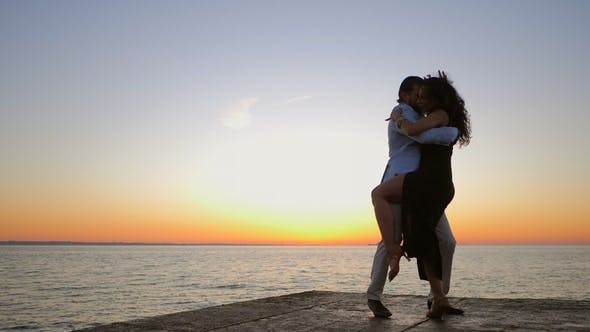 Thumbnail for Silhouettes of Young Hispanic Couple Against Sunset Sea Background. Man and Woman Dancing Latin