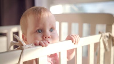 Baby Standing in Bed at Home. Portrait of Baby Girl Stand in Cot. Baby Eyes