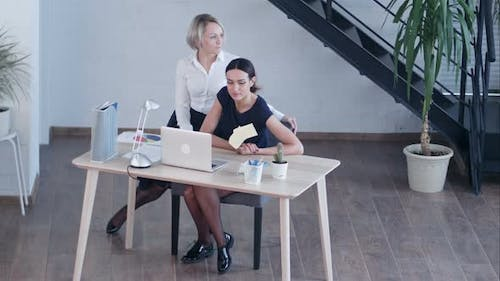 Bored Businesswomen Looking Away While Sitting on Chair