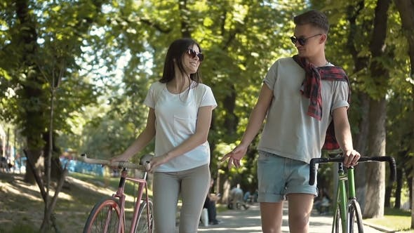 Cover Image for Couple Talking As Walking with Bikes