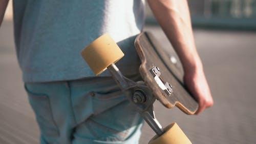 Skateboarder Holds Skateboard